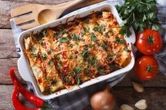 Enchilada messicano in un primo piano orizzontale di vista superiore del piatto di cottura Fotografie Stock