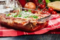 Enchiladas messicani tradizionali con carne di pollo, salsa al pomodoro piccante e formaggio in piatto termoresistente fotografie stock