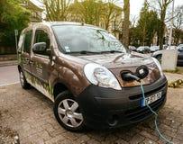Enchufado coche eléctrico de la mini-furgoneta de Renault en la calle eléctrica imagen de archivo libre de regalías