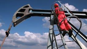 Enchufe de la bomba de la industria de petróleo con un trabajador del aceite almacen de video