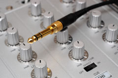 Enchufe del oro en mezclador de la música de DJ Foto de archivo