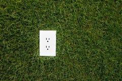Enchufe eléctrico en hierba Foto de archivo