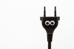 Enchufe eléctrico negro con los ojos googly en el fondo blanco - ascendente cercano Fotos de archivo