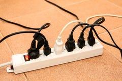 Enchufe eléctrico sobrecargado del zócalo múltiple del mercado de los tableros de poder Imagen de archivo libre de regalías
