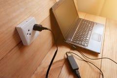 Enchufe el cargador del cable eléctrico del adaptador del ordenador portátil en piso de madera imágenes de archivo libres de regalías