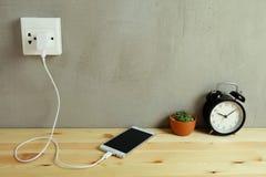 Enchufe el cargador del cordón del adaptador de la toma de corriente del teléfono móvil en de madera imagen de archivo