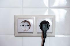 Enchufe negro eléctrico Dos zócalos en un fondo de las tejas blancas foto de archivo