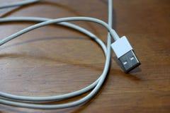 Enchufe usado del USB con el cable en el piso de madera Foto de archivo
