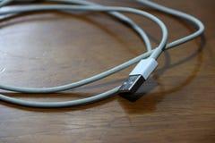 Enchufe usado del USB con el cable en el piso de madera Fotografía de archivo