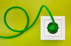 Enchufe verde en el socket de potencia blanco Fotos de archivo libres de regalías