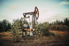 Enchufe viejo de la bomba en el campo petrolífero situado en el bosque Fotografía de archivo