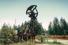 Enchufe viejo de la bomba en el campo petrolífero situado en el bosque Imágenes de archivo libres de regalías