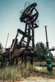 Enchufe viejo de la bomba en el campo petrolífero situado en el bosque Imagen de archivo libre de regalías