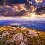 Enciéndase en la cuesta de montaña de piedra con el bosque en la puesta del sol Imagenes de archivo