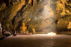 Enciéndase en la cueva con sentar la estatua de Buda Imagenes de archivo