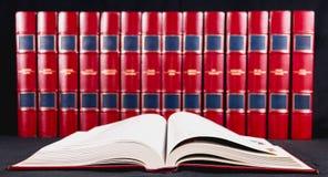 Enciclopédias velhas no fundo preto fotos de stock royalty free