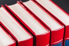 Enciclopédias velhas no fundo preto fotos de stock