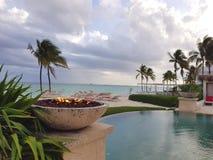 Encienda el hoyo al lado de una piscina del infinito en la playa en la isla de Nassau, Bahamas fotos de archivo libres de regalías