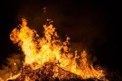 Encienda las llamas con las chispas y la ascua en fondo negro foto de archivo