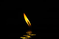 Encienda una vela y la luz refleja Imagenes de archivo