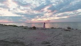 Encima de la opinión la mujer joven dulce con maquillaje chispeante en un baile rosado del vestido con las bombas de humo en el b almacen de metraje de vídeo