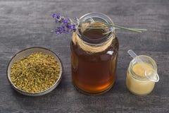 Encima de vista del iin de oro del polen de la abeja a la taza con la jalea real y la miel en vidrio del tarro Foto de archivo