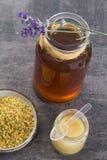 Encima de vista del iin de oro del polen de la abeja a la taza con la jalea real y la miel en vidrio del tarro Fotografía de archivo libre de regalías