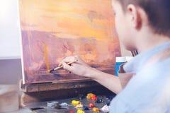 Encima de y pintor que viene que trabaja en imagen abstracta en estudio Imágenes de archivo libres de regalías