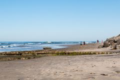 People Jog and Walk on Swami`s Beach in Encinitas, California. ENCINITAS, CALIFORNIA/USA - FEBRUARY 24, 2018:  People jog and walk on Swami`s Beach at low tide Royalty Free Stock Image
