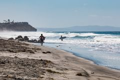 Two Male Surfers on Beacon`s Beach in Encinitas, California. ENCINITAS, CALIFORNIA/USA - OCTOBER 4, 2016:  Two male surfers head out to sea carrying surfboards Royalty Free Stock Photos
