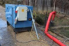 Enclosed industrial power generator powering large water pump. Enclosed industrial power generator providing electrical power to large water pumps with strong Stock Image