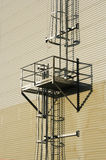 Enclosed ladder on outside of. Enclosed metal ladder and platform on side of metal clad building Stock Photography