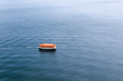 Enclosed rigid lifeboat awaiting rescue in the wide expanse of t Royalty Free Stock Photo