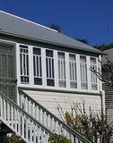 Enclosed verandah on Queenslander. White painted windows for airflow ti enckosed verandah on old Queenslander.  Wooden stairs in green and white leading to Royalty Free Stock Photos