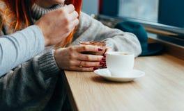 Encontrándose en un café, muchacha pelirroja que bebe el chocolate caliente imagenes de archivo