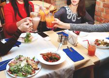 Encontrando amigos das mulheres no restaurante para o jantar As meninas relaxam e bebem cocktail fotografia de stock