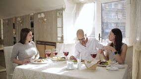Encontrando amigos no restaurante Amigos felizes que comem e que bebem no restaurante Quatro amigos no restaurante, comem vídeos de arquivo