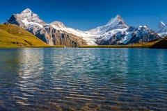Encontrando Bachalpsee ao caminhar primeiramente aos cumes de Grindelwald Bernese, Suíça imagem de stock
