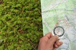 encontrando a posição direita na floresta com um compasso fotografia de stock royalty free