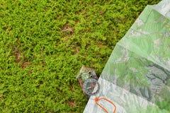 Encontrando a posição direita na floresta com um mapa e kompass Foto de Stock