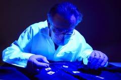 Encontrar das evidências na camisa do criminoso sob a luz UV pelo técnico imagens de stock royalty free