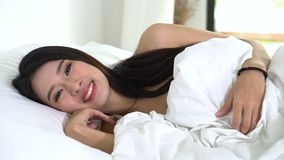 Encontro asiático bonito do sono da jovem mulher na cama com cabeça na câmera de filtração movente acordando confortável e feliz  video estoque