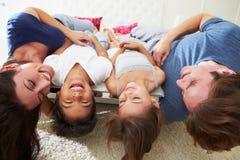 Encontro da família de cabeça para baixo na cama nos pijamas junto Fotografia de Stock