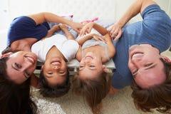 Encontro da família de cabeça para baixo na cama nos pijamas junto Foto de Stock
