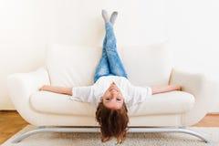 Encontro da mulher de cabeça para baixo em um sofá Fotos de Stock Royalty Free