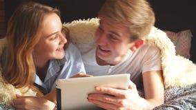 Encontro de riso dos pares loving na cama e utilização da tabuleta vídeos de arquivo