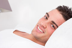 Encontro de sorriso do homem sensual considerável na cama Foto de Stock