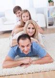 Encontro feliz da família empilhado no tapete na sala de visitas imagens de stock royalty free