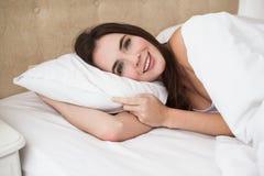 Encontro moreno bonito na cama que sorri na câmera Imagem de Stock Royalty Free