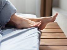 Encontro nos pés fêmeas da cama sob a cobertura imagens de stock royalty free